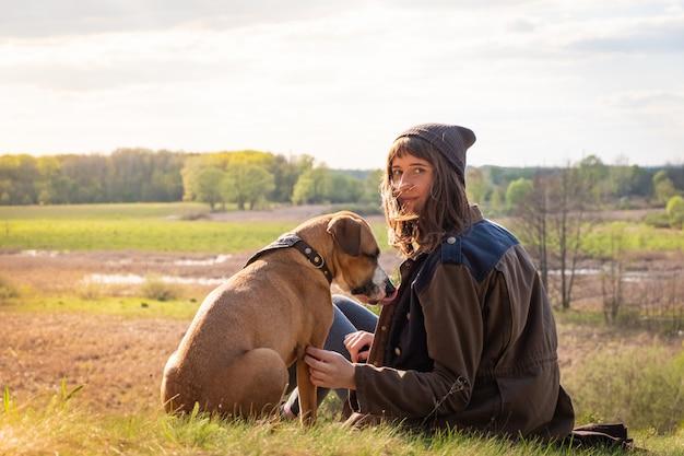 Молодая самка вместе со стаффордширским терьером на лугу на теплый солнечный день
