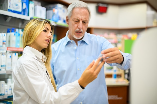 Young female pharmacist dealing with a customer