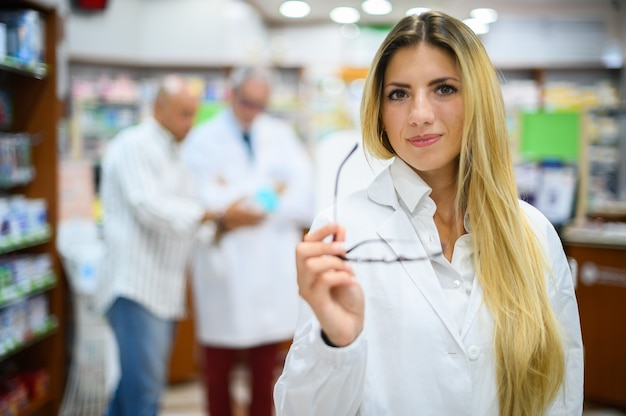 Young female pharmacist smiling in her store holding her eyeglasses