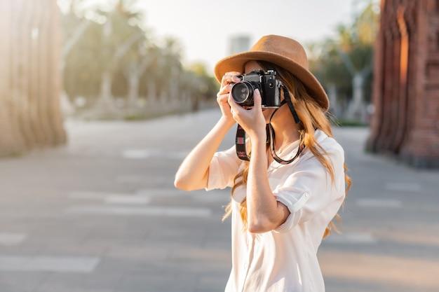 Молодая женщина-фотограф фотографирует старинной камерой