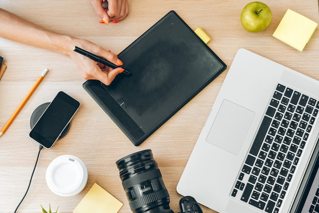 Young female photographer working at home office