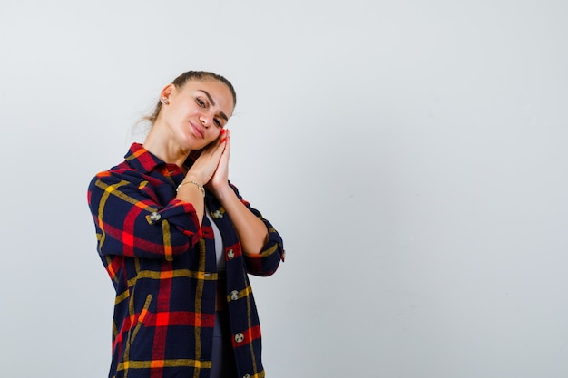 Молодая женщина кладет лицо подушками на руки в кроп-топе, клетчатой рубашке и выглядит сонной, вид спереди.