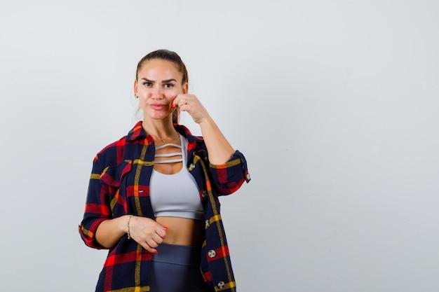 若い女性がクロップトップで頬をつまんで、市松模様のシャツを着て、かわいく見えます。正面図。