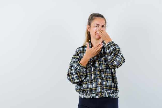 Giovane femmina che pizzica il naso a causa del cattivo odore in maglietta, pantaloncini e sembra disgustata. vista frontale.