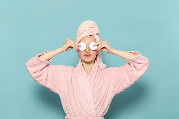 Young female in pink bathrobe after shower covering her eyes on blue