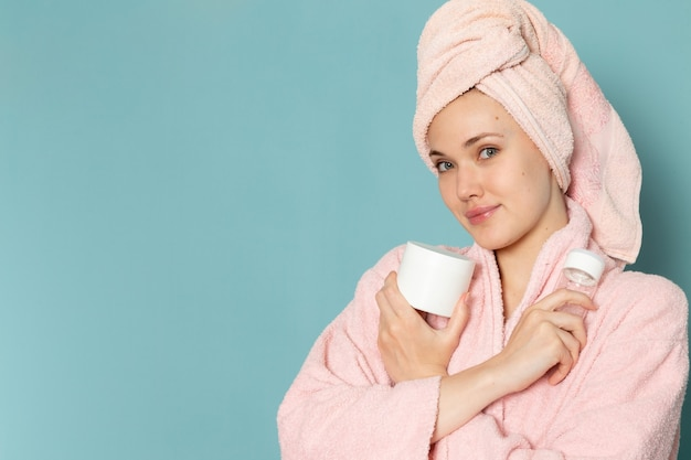 Young female in pink bathrobe after shower holding cream spray on blue