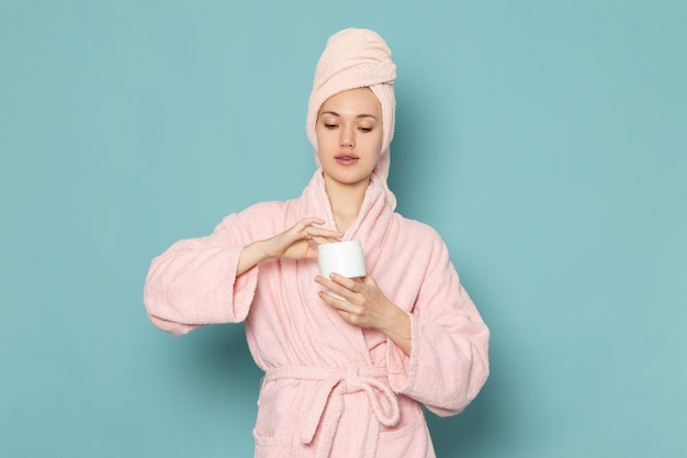 Young female in pink bathrobe after shower holding cream using it on blue