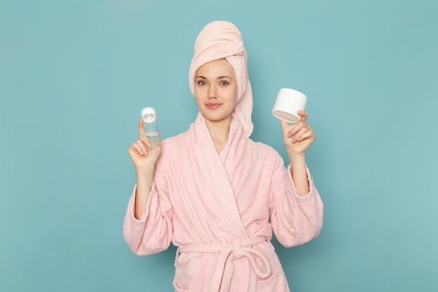 Young female in pink bathrobe after shower holding spray and cream on blue