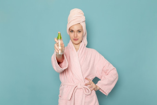 Young female in pink bathrobe after shower holding spray and smiling on blue