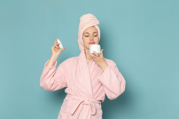 Young female in pink bathrobe after shower holding and using cream on blue