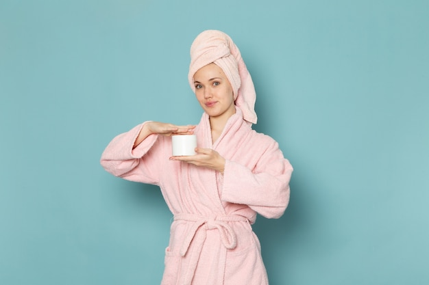 Young female in pink bathrobe after shower holding white cream on blue