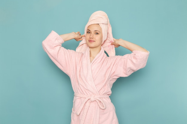 Young female in pink bathrobe after shower smiling on blue