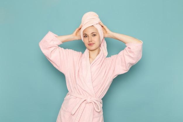 Giovane donna in accappatoio rosa dopo la doccia sorridente e in posa sul blu