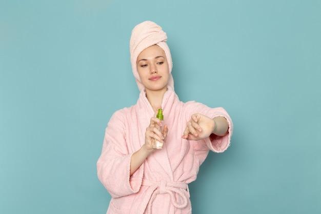 Giovane donna in accappatoio rosa utilizzando spray per il corpo sul blu
