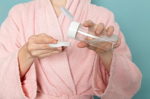 Giovane donna in accappatoio rosa utilizzando detergente per il trucco sul blu