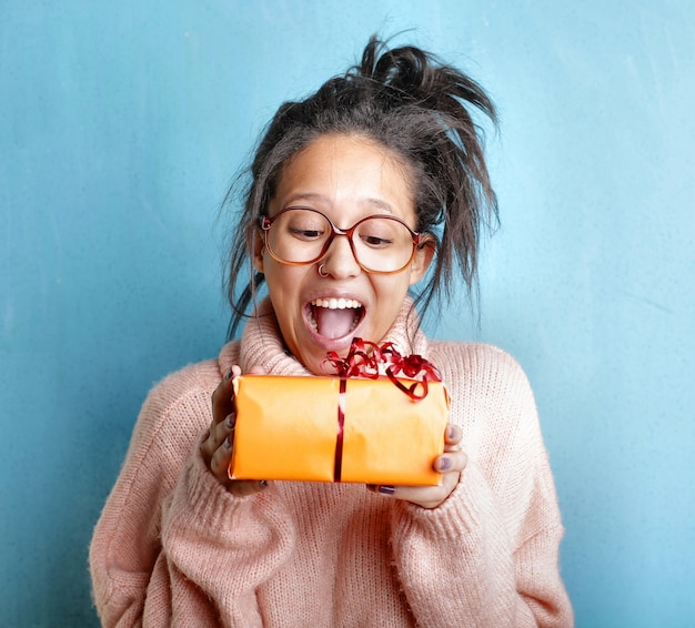 Young female in a pink sweater expressing happiness while holding a gift box