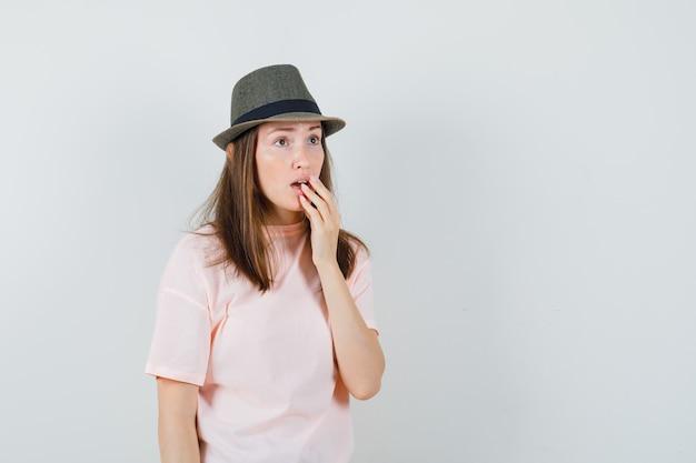 Giovane donna in maglietta rosa, cappello tenendo la mano sulla bocca aperta e guardando meravigliato, vista frontale.