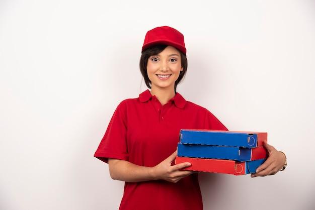 Молодой женский работник доставки пиццы, держа три картона пиццы.