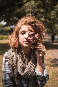 Young female inplaid shirt holding crimson leaf in park