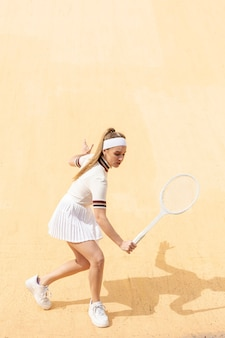 Young female playing tennis on field