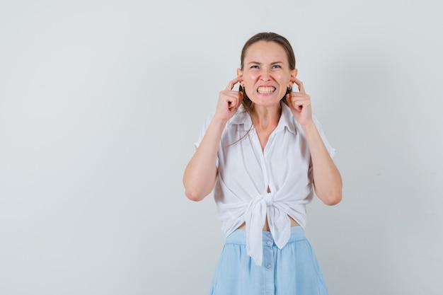 ブラウス、スカートに指で耳を塞いでイライラしている若い女性