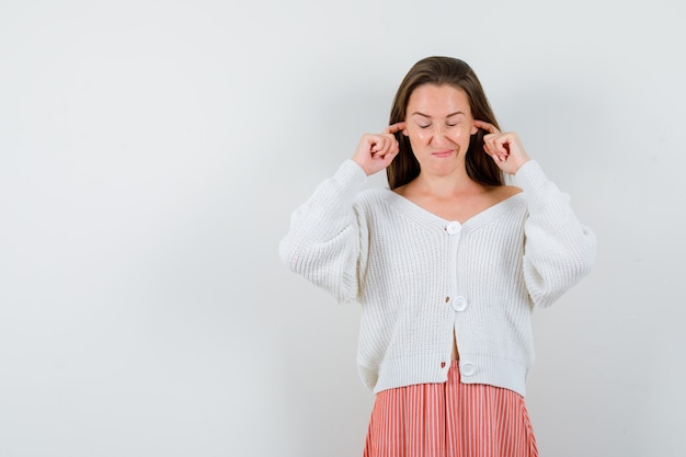 カーディガンとスカートの指で耳を塞ぐ若い女性は、孤立して退屈そうに見えます