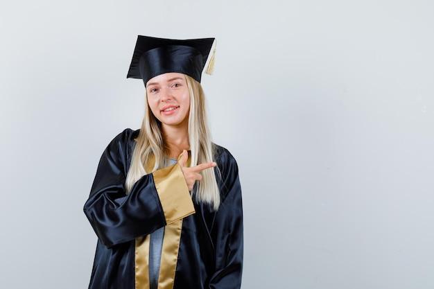 Giovane donna che indica da parte in uniforme laureata e sembra allegra.