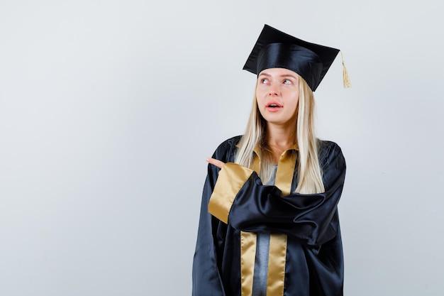 Giovane donna che indica da parte in uniforme laureata e sembra pensierosa.