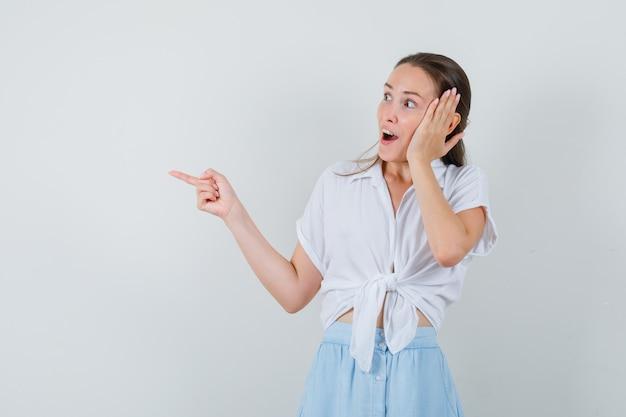 ブラウス、スカートで脇を指して、驚いて見える若い女性