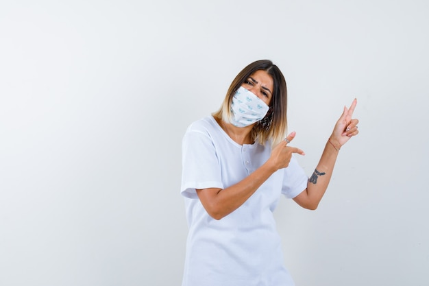 Молодая женщина указывая в сторону в футболке, маске и нерешительно глядя, вид спереди.