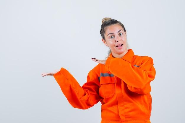 労働者の制服を着て何かを見せるために脇を向いて前向きに見える若い女性。正面図。