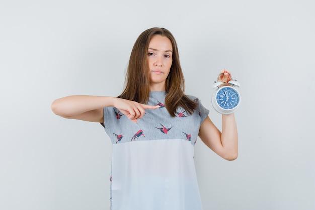 Tシャツの目覚まし時計を指して、注意深く見ている若い女性、正面図。