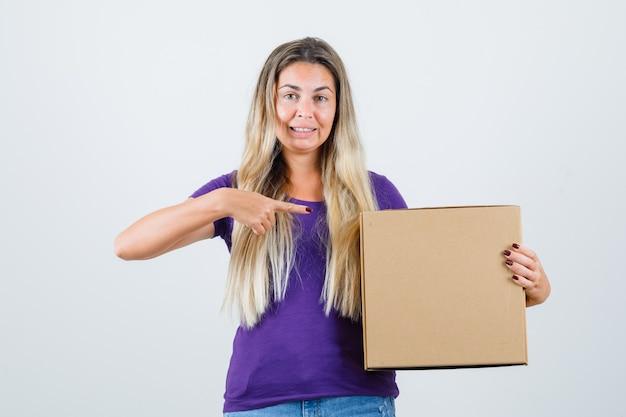 紫のtシャツのボックスを指して、気配りの若い女性。正面図。