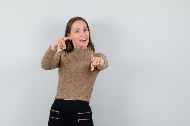 Молодая женщина, указывая на камеру в золотой блузке и глядя веселый, вид спереди. место для текста