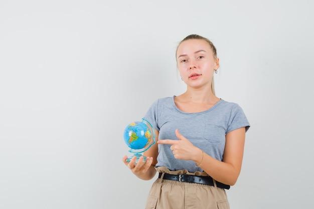 Молодая женщина, указывая на земной шар в футболке, штанах и уверенно глядя. передний план.