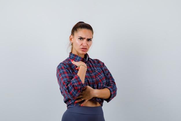 市松模様のシャツ、パンツで自分を指差して躊躇している若い女性、正面図。