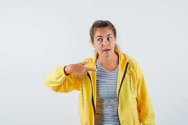 ジャケット、tシャツで自分自身を指して、混乱しているように見える若い女性。正面図。