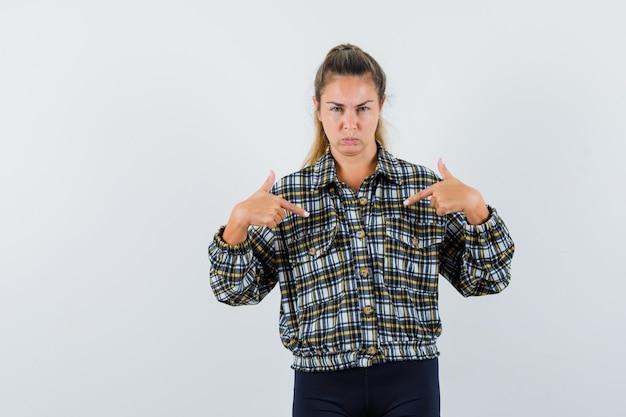 シャツ、ショートパンツで自分自身を指して、疑わしい、正面図を探している若い女性。