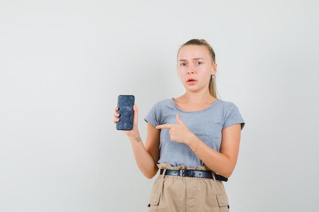 T- 셔츠, 바지에 휴대 전화를 가리키고 의아해 찾고 젊은 여성. 전면보기.