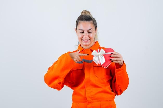 작업자 유니폼에 빨간색 선물을 가리키고 기쁘게 찾고 젊은 여성. 전면보기.