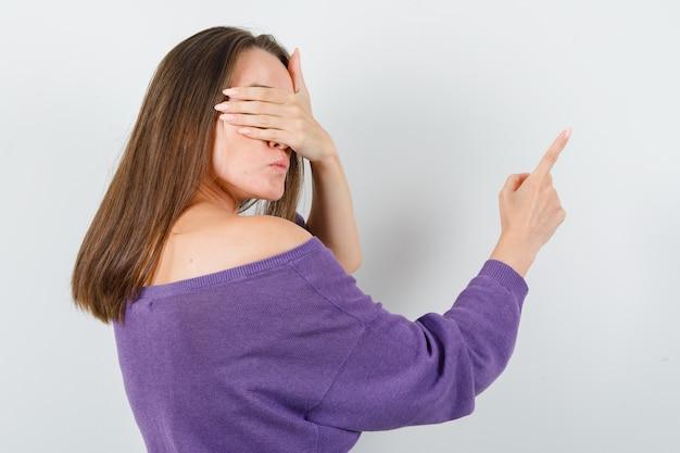 Молодая женщина, указывая на что-то прикрытыми глазами в фиолетовой рубашке.