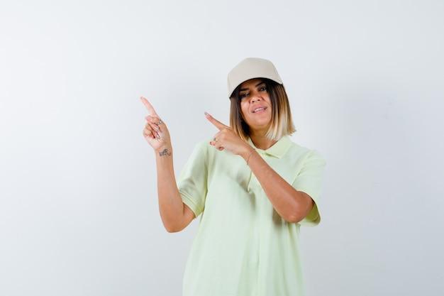 T- 셔츠, 모자에 왼쪽 상단 모서리를 가리키고 쾌활 한, 전면보기를 찾고 젊은 여성.