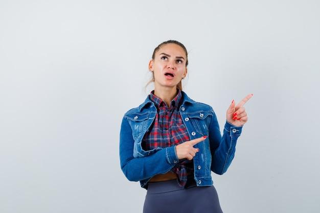 Молодая женщина указывает на верхний правый угол в клетчатой рубашке, куртке, штанах и выглядит озадаченно. передний план.