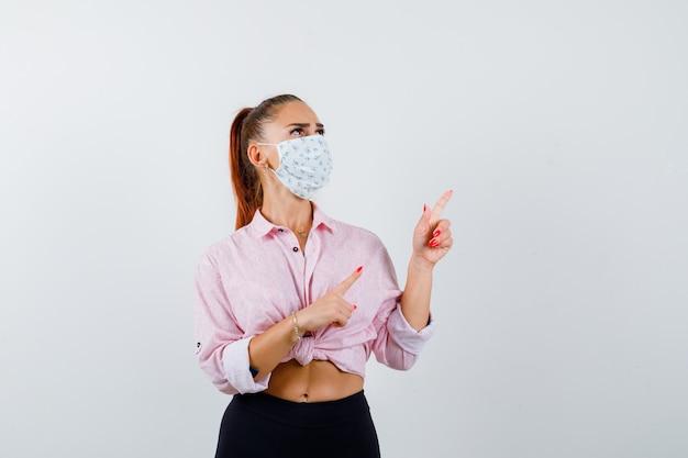 Молодая женщина указывает на верхний правый угол в рубашке, штанах, медицинской маске и выглядит уверенно. передний план.