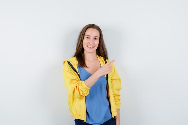 Tシャツ、ジャケットの右上隅を指して、自信を持って、正面図を探している若い女性。