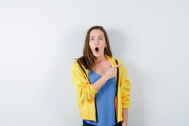 Tシャツ、ジャケットの右上隅を指して、驚いて見える若い女性。正面図。