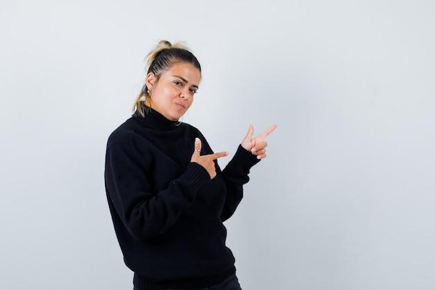 Молодая женщина указывая на верхний правый угол в свитере с высоким воротом и выглядит уверенно. передний план.