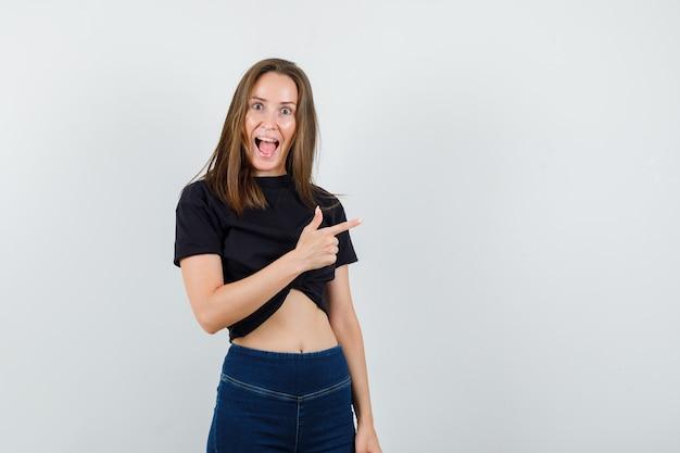 黒のブラウス、ズボンを着て、幸せそうに見える若い女性。