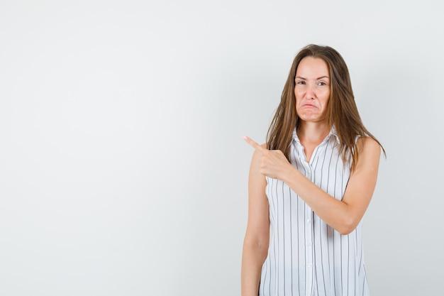 Молодая женщина указывая прочь в футболке и глядя печально. передний план.