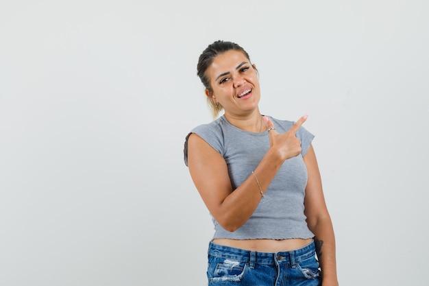 T- 셔츠, 반바지에 멀리 가리키는 쾌활한 찾고 젊은 여성